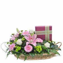 A basket brimming with flowers accompanied by a quality box of chocolates