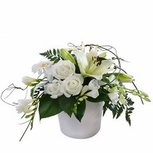 Modern arrangement in whites and greens in a ceramic container